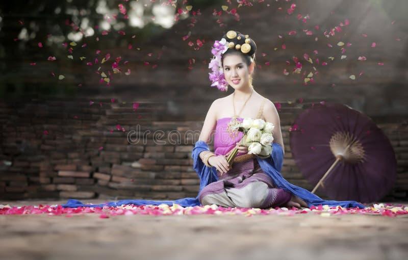 Belle femme dans la robe traditionnelle thaïlandaise tenant la fleur de lotus photographie stock