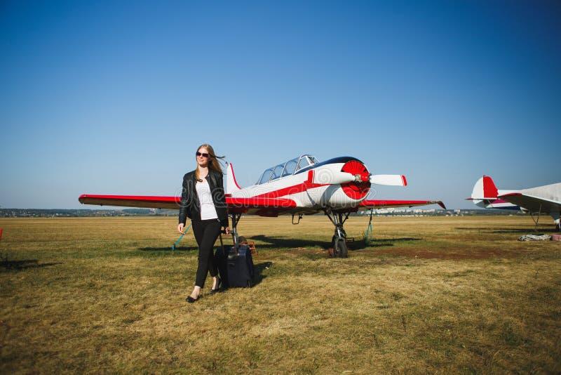 Belle femme dans la veste en cuir noire se tenant devant de petits avions de vintage photos stock