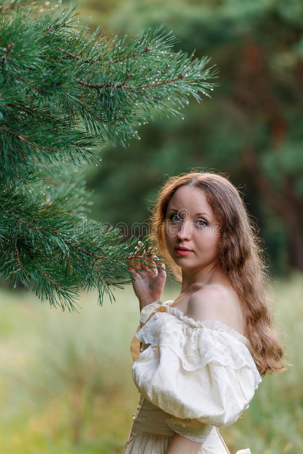 Belle femme dans le beige de robe de vintage Fille mignonne dans la longue robe marchant dans une forêt de pin le style de la rei image libre de droits