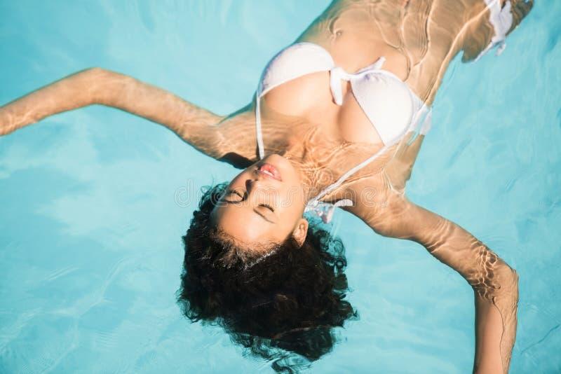 Belle femme dans le bikini blanc flottant dans la piscine photo stock