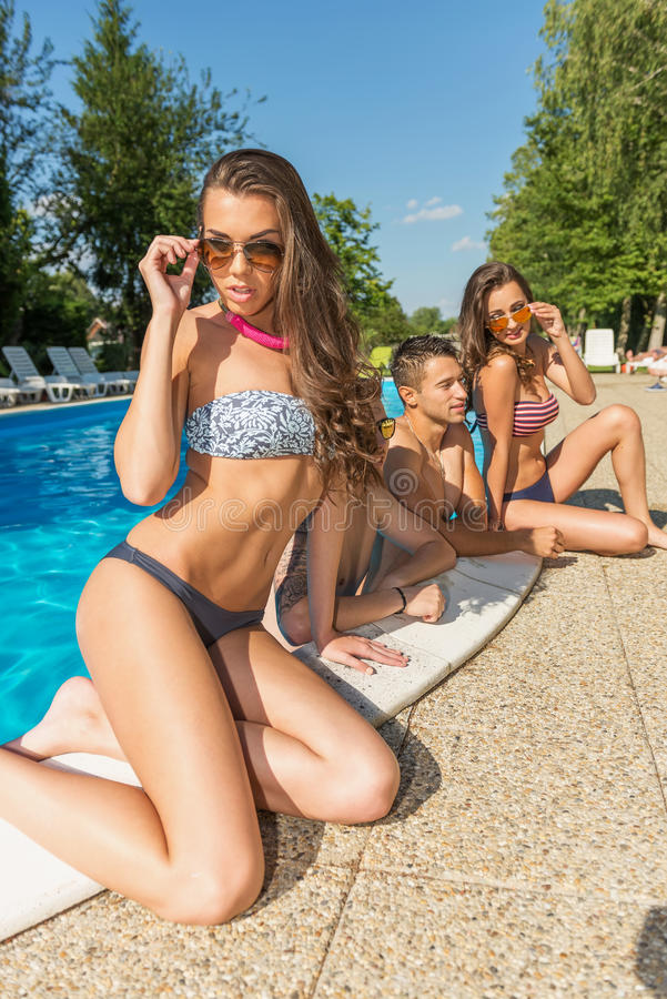 Belle femme dans le bikini posant au bord de la piscine derrière ses amis images libres de droits