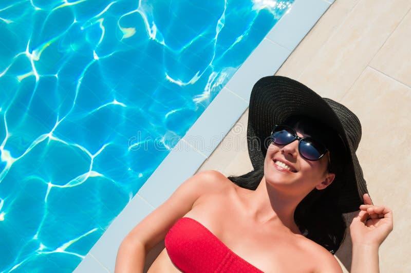 Belle femme dans le bikini rouge détendant près de la piscine images libres de droits