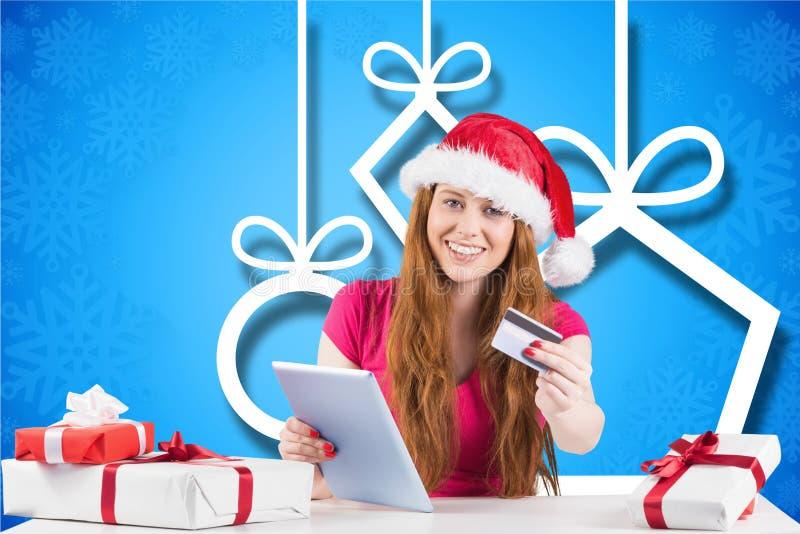 Belle femme dans le chapeau de Santa faisant des achats en ligne avec la carte de crédit sur le comprimé numérique photographie stock libre de droits