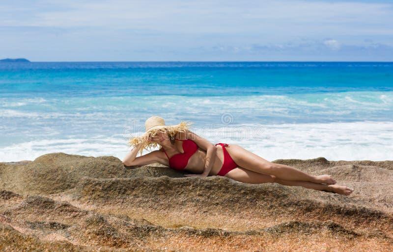Belle femme dans le chapeau du soleil de paille et le maillot de bain rouge, Seychelles photographie stock