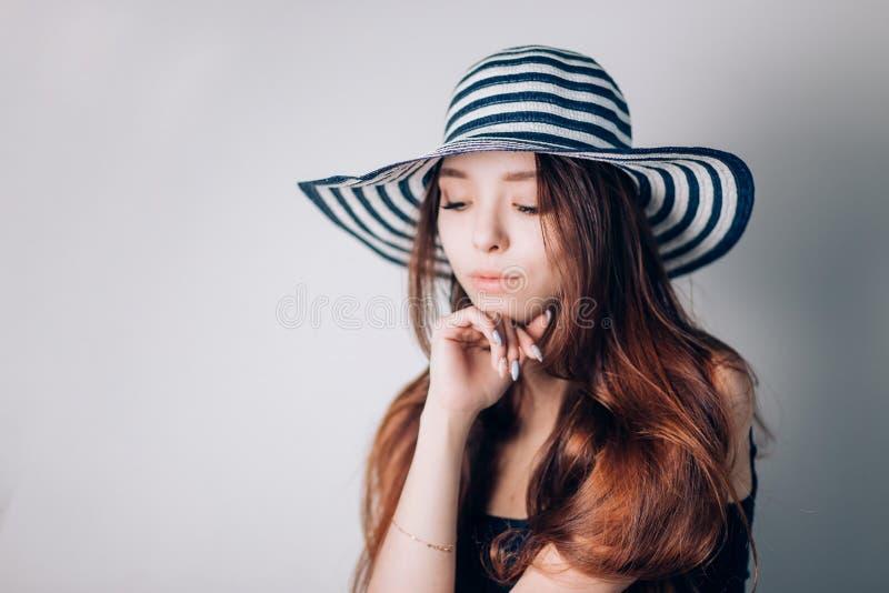 Belle femme dans le chapeau regardant vers le bas avec un sourire sur le fond blanc Été, vacances, mer, l'espace de copie, horizo photos stock