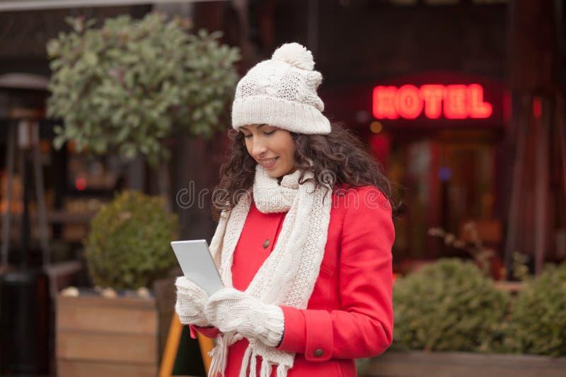 Belle femme dans le chapeau rouge de manteau et de laine et gants avec le smartph photographie stock