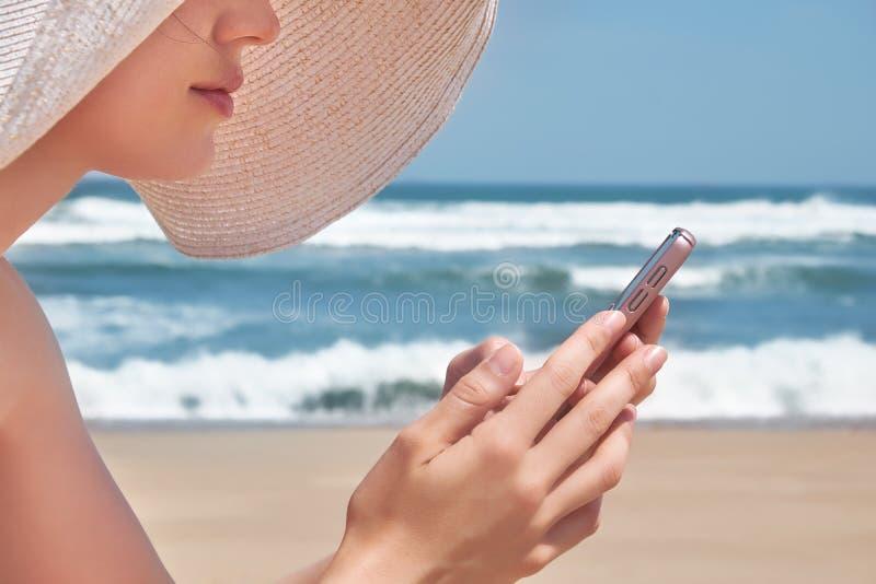 Belle femme dans le chapeau utilisant son téléphone portable tout en détendant sur la plage photos libres de droits