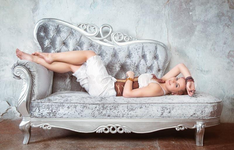 Belle femme dans le corset et des pantalons sur le sofa photo libre de droits