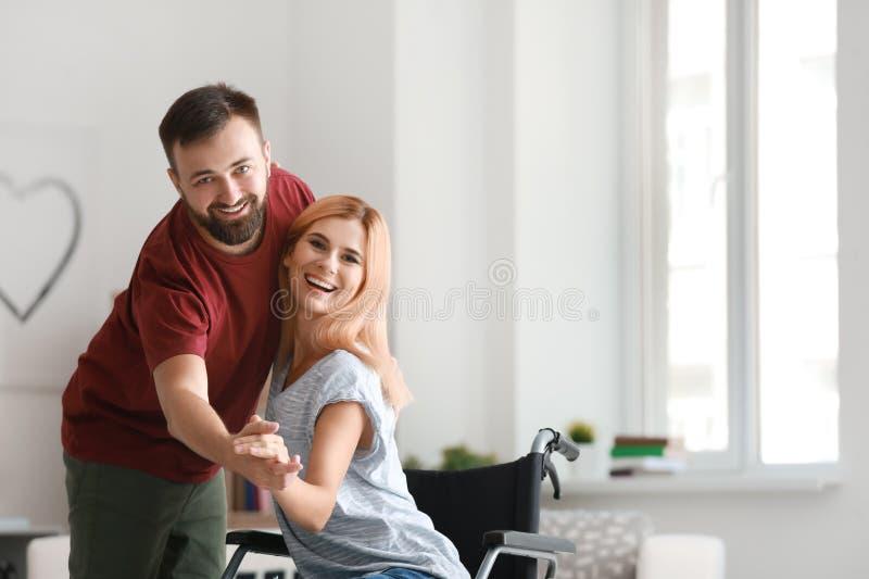 Belle femme dans le fauteuil roulant avec l'homme dansant à la maison photo stock