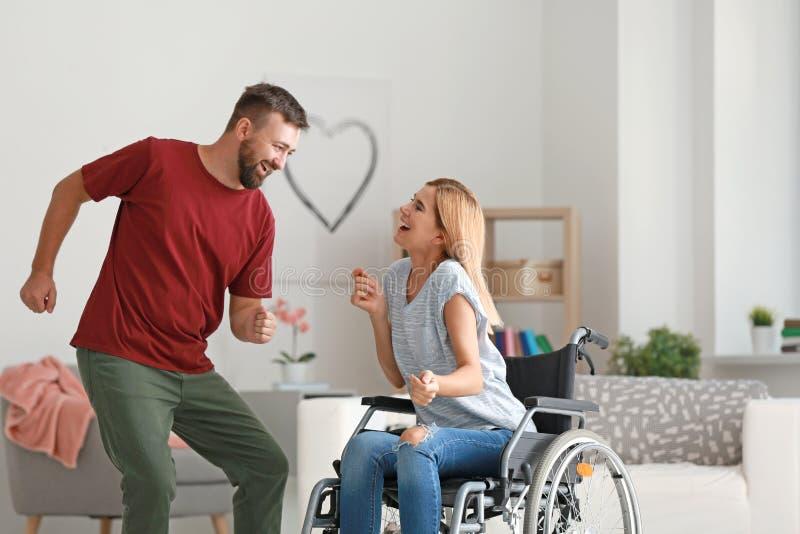 Belle femme dans le fauteuil roulant avec l'homme dansant à la maison image libre de droits