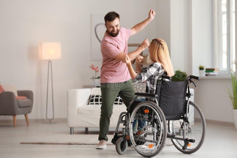 Belle femme dans le fauteuil roulant avec l'homme dansant à la maison image stock