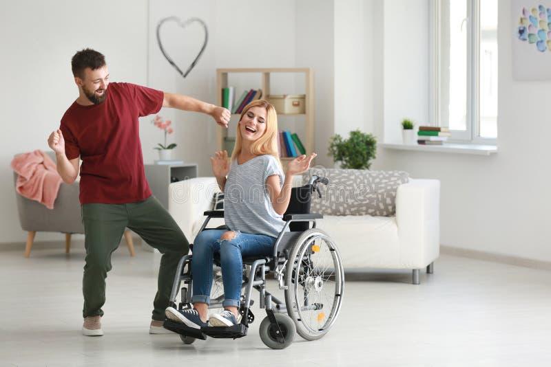 Belle femme dans le fauteuil roulant avec l'homme dansant à la maison photo libre de droits