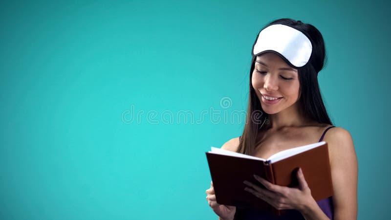 Belle femme dans le livre de lecture de pyjamas avant le sommeil, rituel de détente heure du coucher images stock
