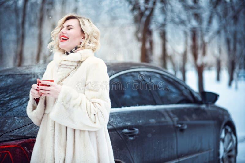 Belle femme dans le manteau de fourrure blanc luxueux buvant du café chaud le jour et rire d'hiver neigeux photographie stock