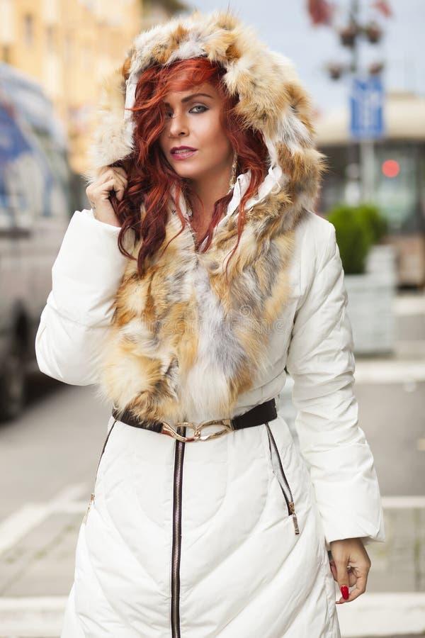 Belle femme dans le manteau de fourrure sur la rue image libre de droits