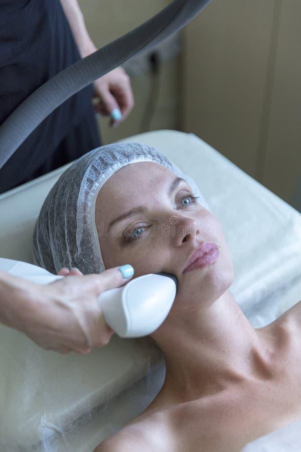 Belle femme dans le salon de beauté professionnel pendant la procédure de levage par radio photographie stock