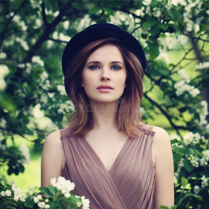 Belle femme dans un chapeau noir dehors Portrait de ressort image libre de droits