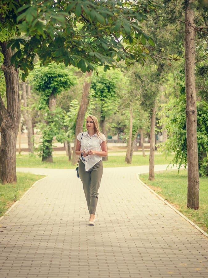 Belle femme dans un costume dans l'allée du parc de ville images libres de droits