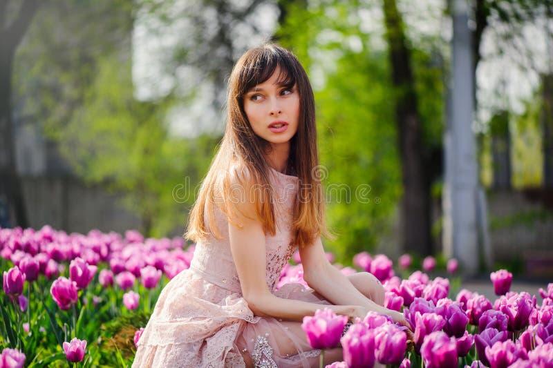 Belle femme dans un domaine des tulipes photos stock