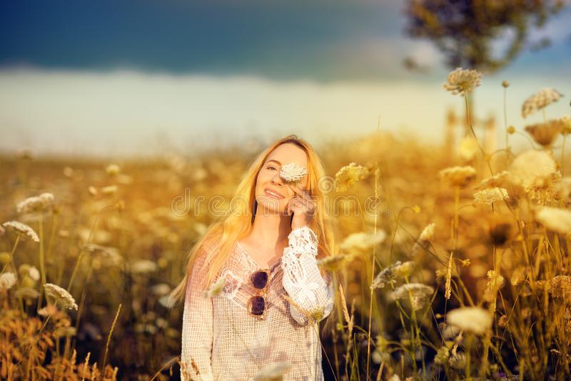 Belle femme dans un pré de fleur avec les lunettes de soleil et la fleur, convoitise pendant la vie photos stock