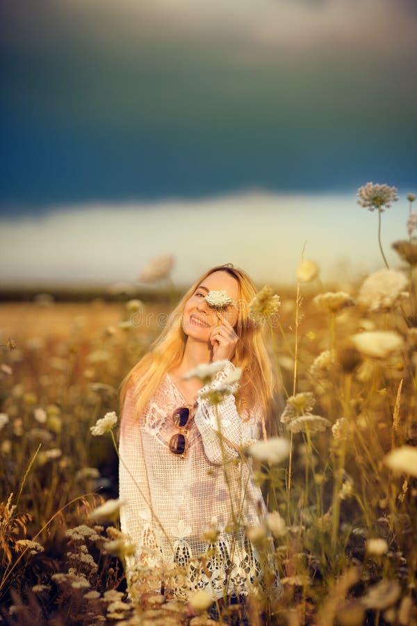 Belle femme dans un pré de fleur avec les lunettes de soleil et la fleur, convoitise pendant la vie images stock