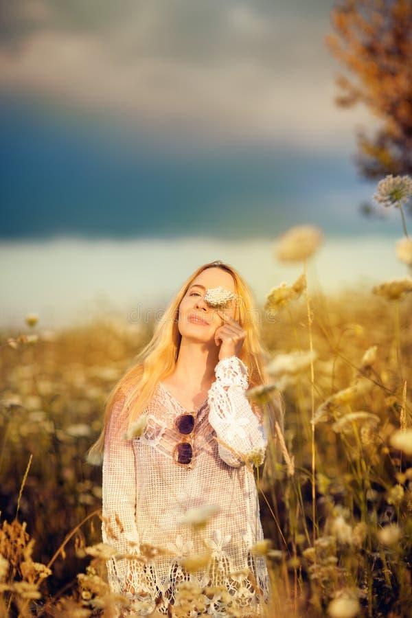 Belle femme dans un pré de fleur avec les lunettes de soleil et la fleur, convoitise pendant la vie photographie stock