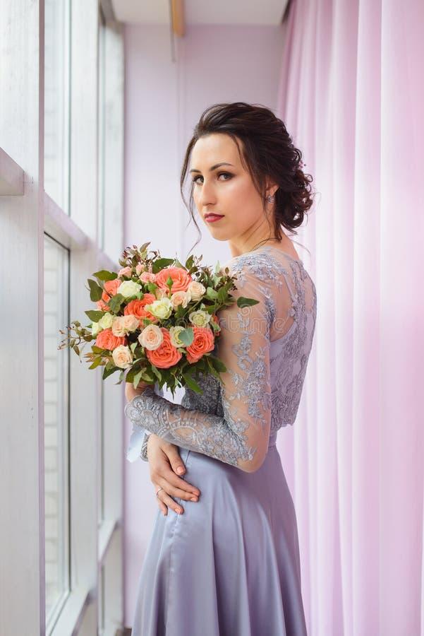 Belle femme dans une robe de prune posant avec un bouquet des roses image stock