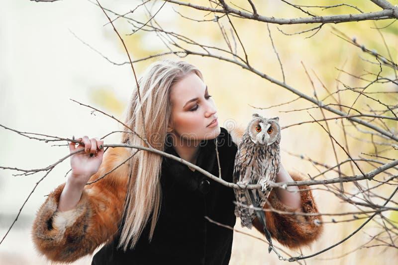 Belle femme dans une robe noire avec un hibou sur son bras Blonde avec de longs cheveux en nature tenant un hibou Fille sensible  photographie stock