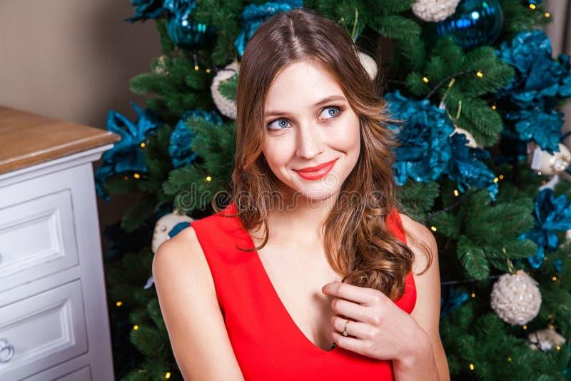 Belle femme dans une robe rouge, recherchant et rêvant photos stock