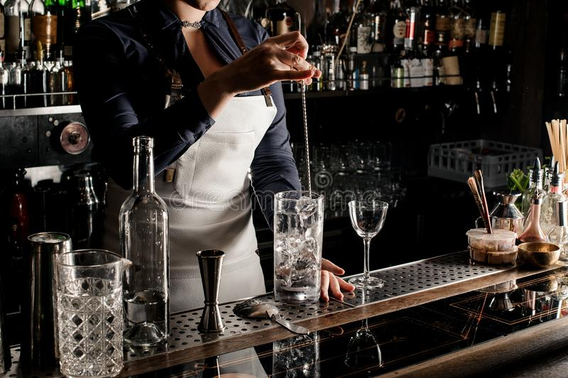 Belle femme de barman remuant la boisson fraîche d'été image stock