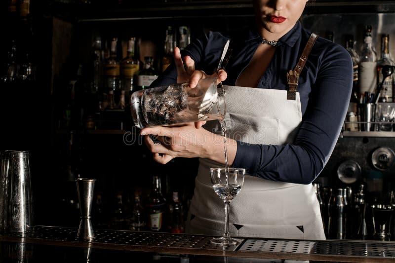 Belle femme de barman versant le cocktail frais dans un verre images stock