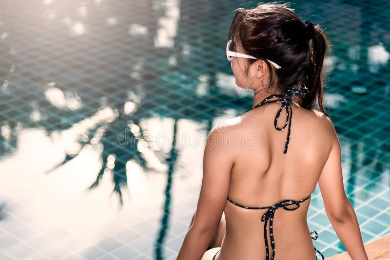 Belle femme de brune arrière de vue appréciant le whi de maillot de bain et de chapeau photographie stock