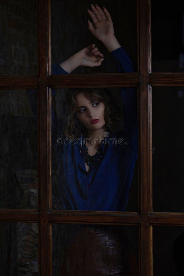 Belle femme de brune avec le chemisier de port et le collier de cheveux bouclés posant derrière la porte en verre photo stock