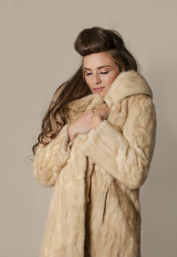 Belle femme de brune avec le maquillage tribal et le manteau de fourrure image stock
