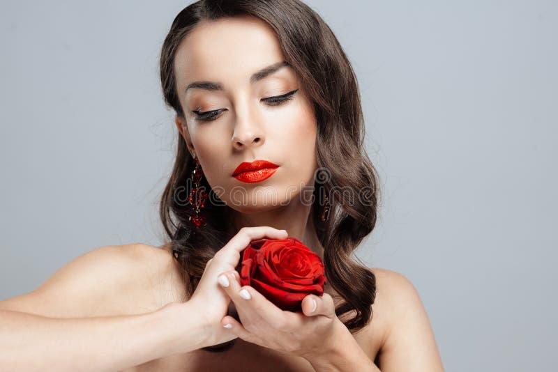 Belle femme de brune avec le rouge à lèvres rouge sur des lèvres La fille en gros plan avec s'est levée photo stock
