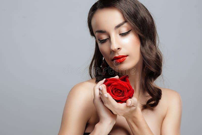 Belle femme de brune avec le rouge à lèvres rouge sur des lèvres La fille en gros plan avec s'est levée photographie stock