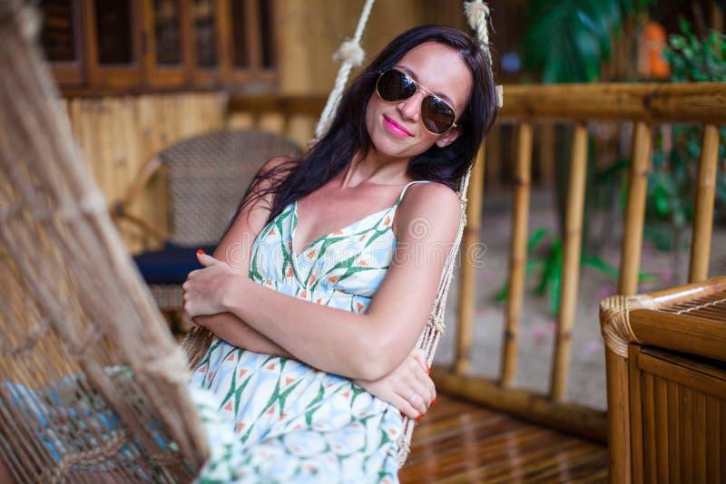 Belle femme de brune détendant dans l'hamac à l'hôtel exotique sur Philippines photos stock