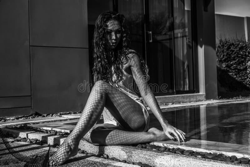 Belle femme de brune dans la piscine extérieure photos stock