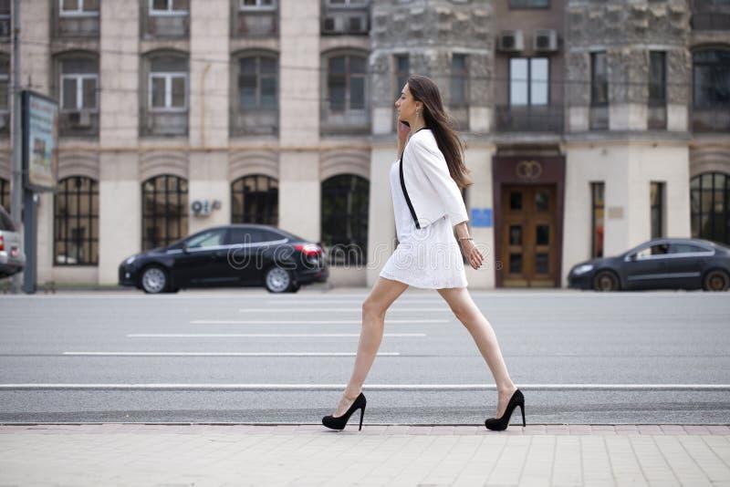 Belle femme de brune dans la robe blanche marchant sur la rue photo stock