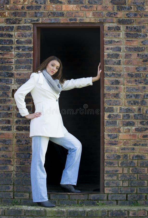 Belle femme de brune dans le manteau blanc et des jeans d'hiver, posant en porte de grange photo libre de droits