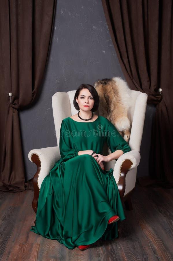 Belle femme de brune dans une robe verte en soie posant se reposer dans une chaise de vintage Style de Bohème photos stock