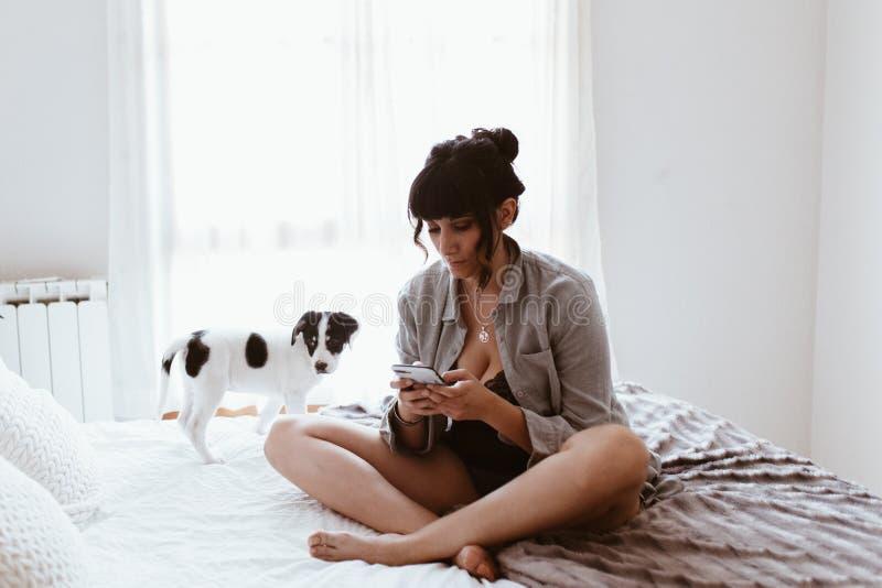 Belle femme de brune employant le mobile de smartphone avec son chiot doux dans la chambre ? coucher photo stock