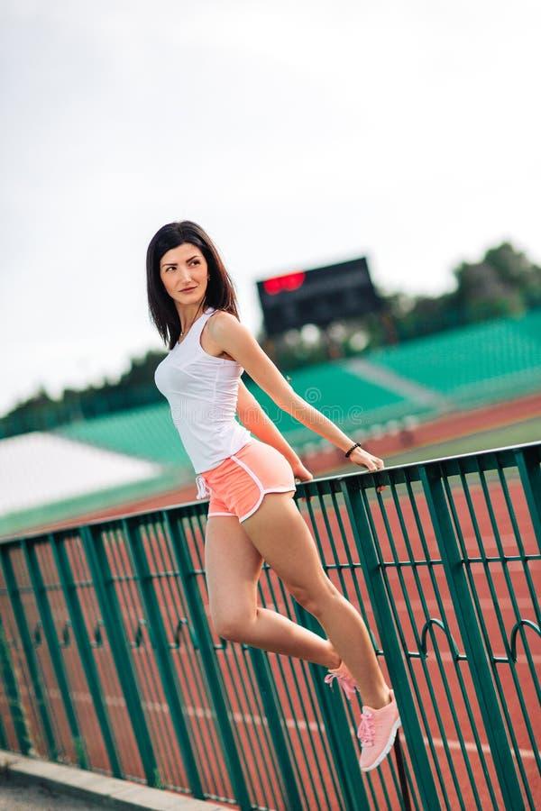 Belle femme de brune de forme physique dedans dans les shorts roses et le dessus de réservoir posant près de la voie courante prè photos stock