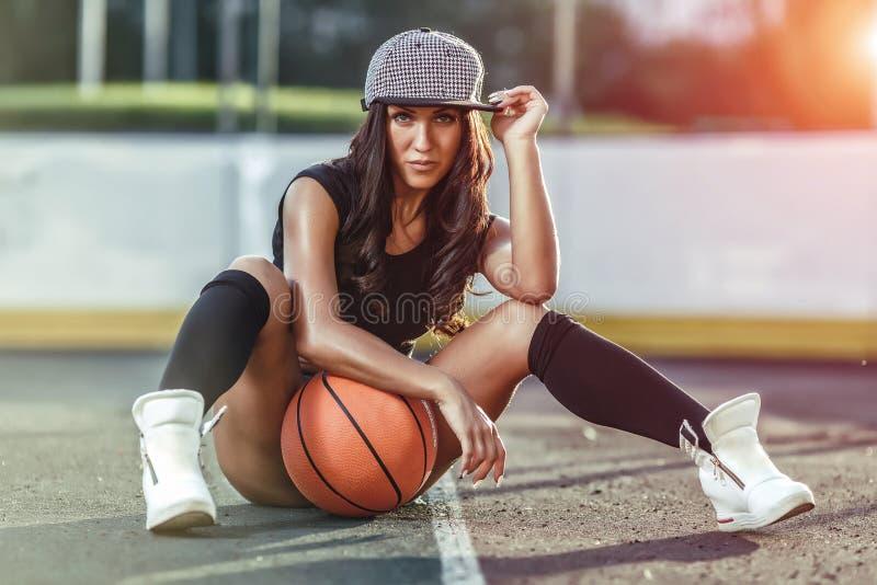 Belle femme de brune jouant le basket-ball sur la cour extérieure image libre de droits