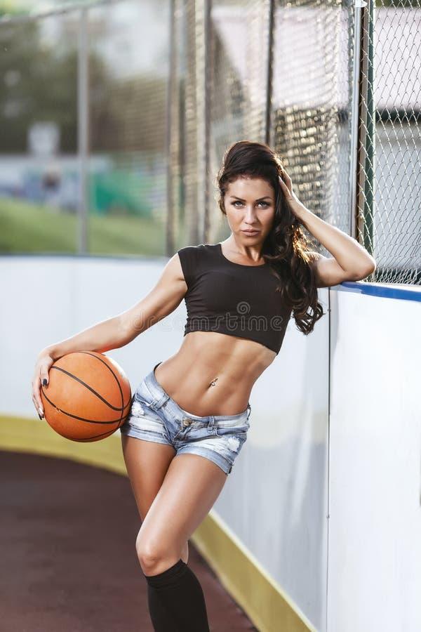 Belle femme de brune jouant le basket-ball sur la cour extérieure photo libre de droits