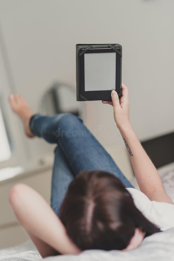 Belle femme de brune tenant l'eBook vide à la maison image libre de droits