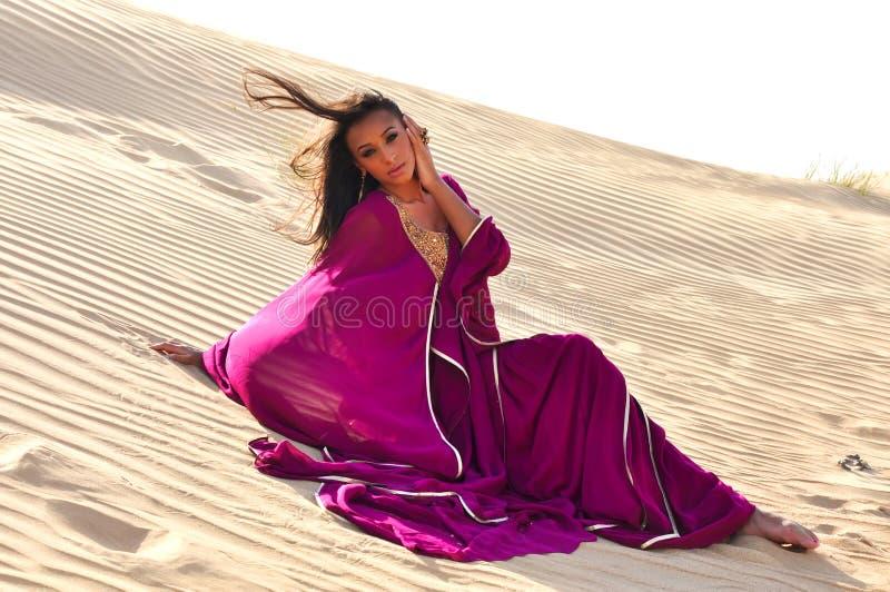 Belle femme de brunette posant dans le désert arabe images stock