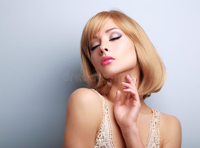 Belle femme de cheveux blonds avec les yeux fermés touchant la peau photo stock