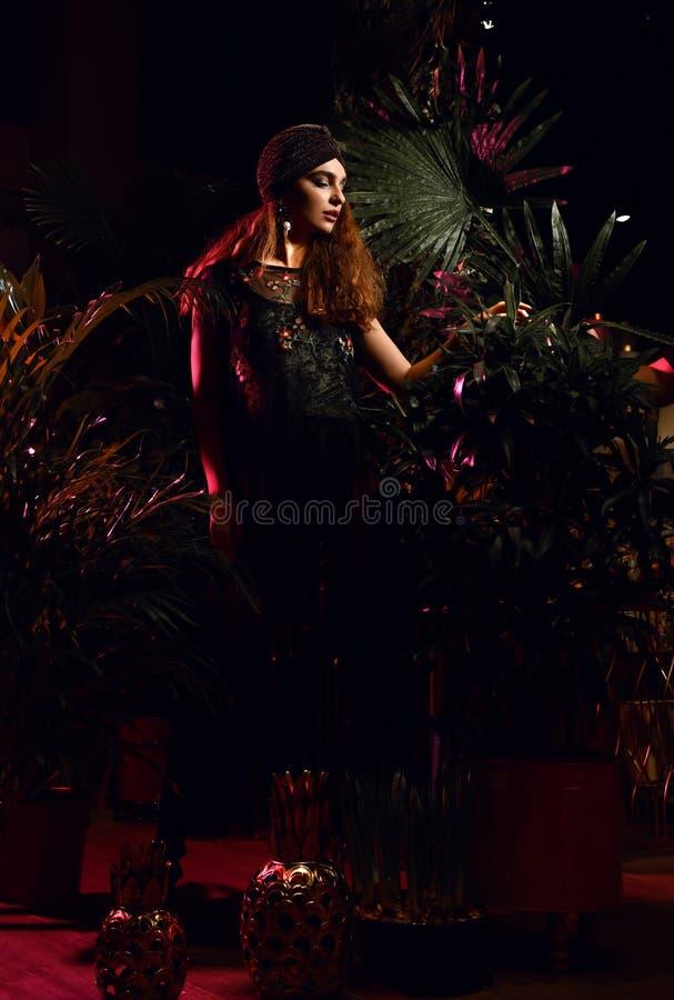 Belle femme de cheveux bouclés de mode posant dans la robe moderne dans la forêt tropicale de feuilles à la nuit image stock