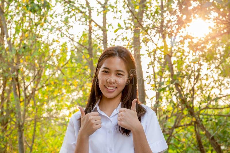 Belle femme de collage souriant avec des pouces avec le fond de lumière du soleil de nature photographie stock libre de droits